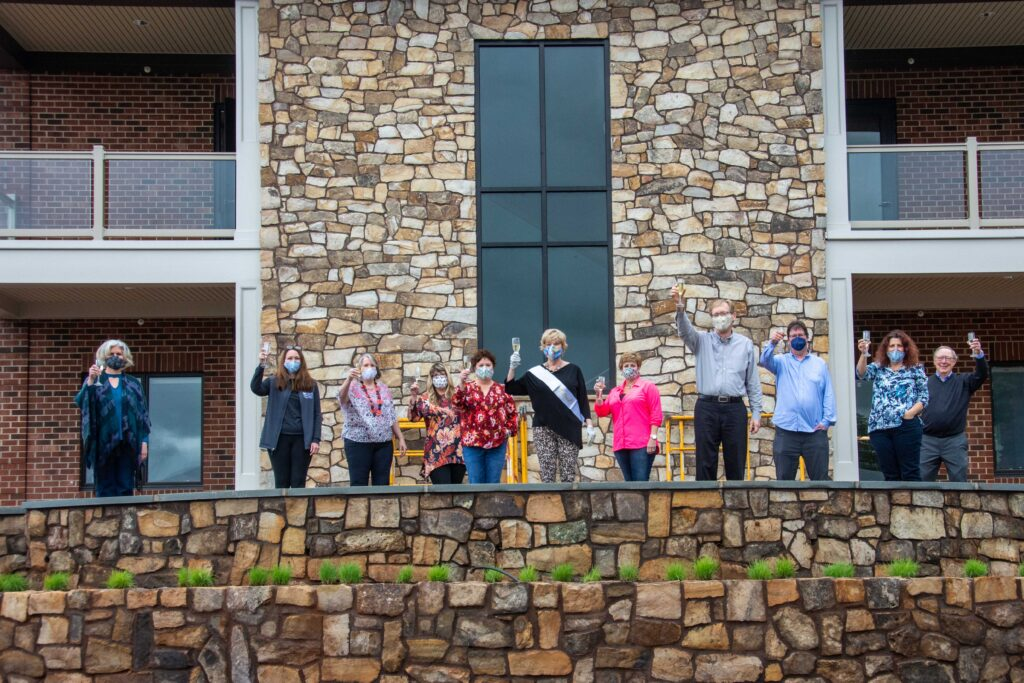 Photo of group of staff members gathered on a stone patio, waving.