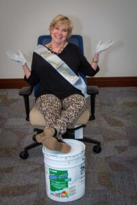 Photo of Mary Jo Monahan wearing a farewell sash and surgical gloves, sitting in an executive office chair with her feet propped up on a paint bucket