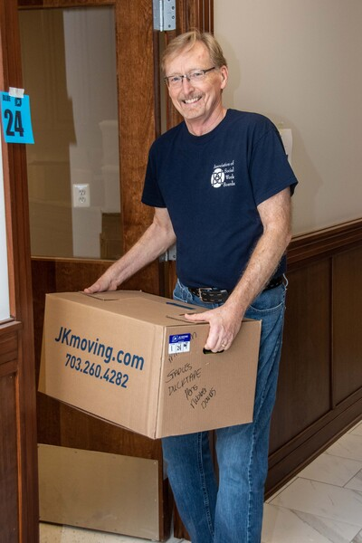 Photo of Dwight Hymans carrying a moving box