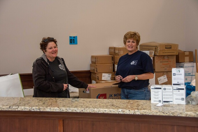 Photo of Heather Foley and Jill Armm standing in front of a pile of moving boxes with a countertop in the foreground